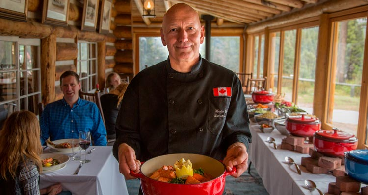 Chef Martin Brenner holds a ceramic pot of food in a historic chalet