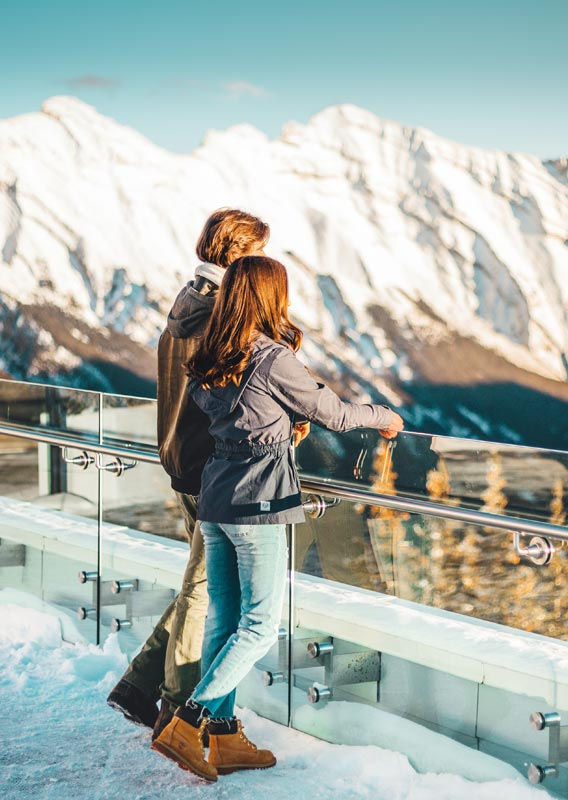 Couple standing at a mountaintop railing looking towards snow-covered peaks.