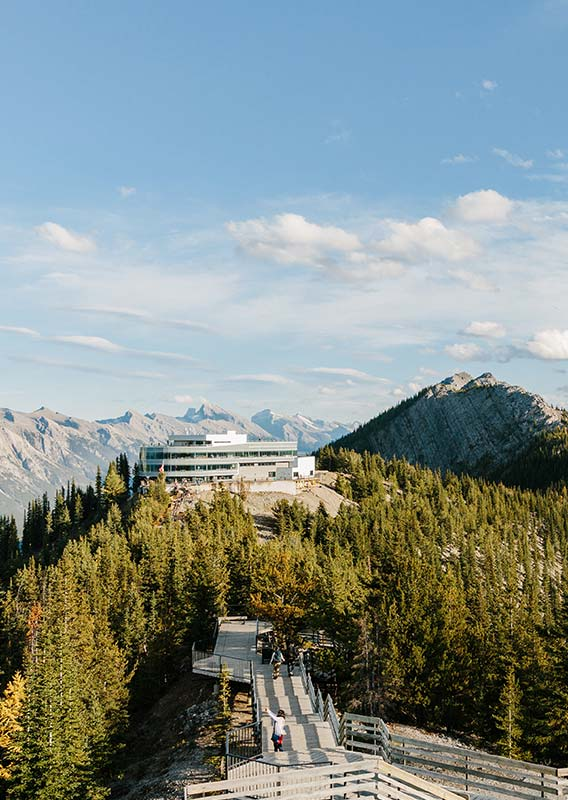 The Banff Gondola summit building atop Sulphur Mountain overlooking forested mountainsides