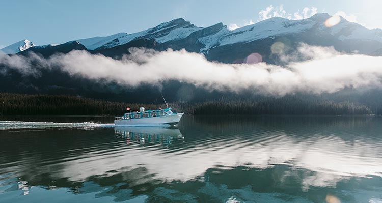 A boat cruises along a crisp lake below a low cloud and snow-covered mountains.