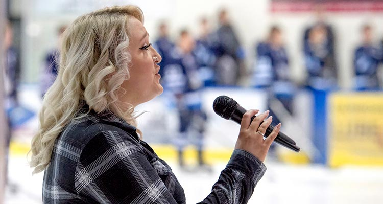 A woman sings at a hockey game.