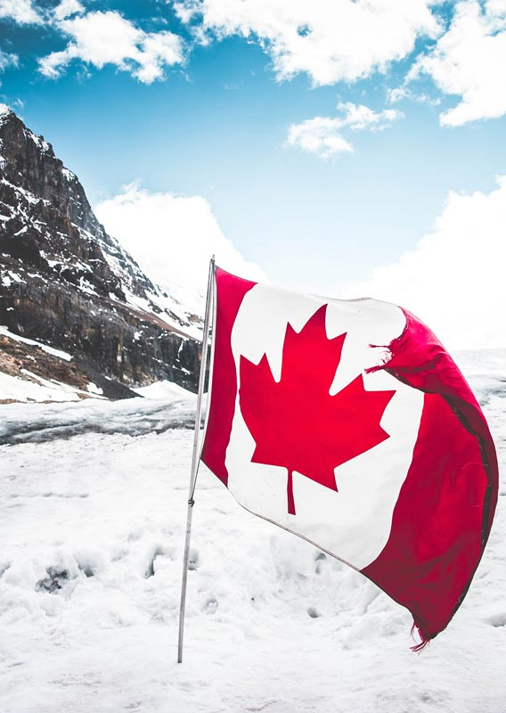 A Canadian flag on a glacier below mountains.
