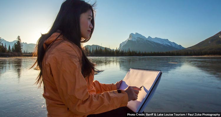 A woman sits near a lake with a drawing pad.