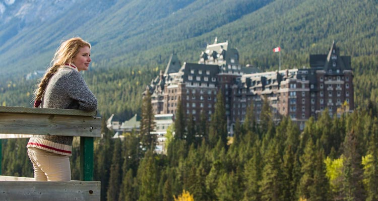 A woman stands at a wooden railing looking towards the Banff Springs Hotel
