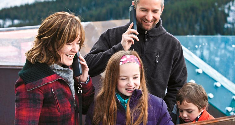 A family listens to audioguides on the Columbia Icefield Skywalk.