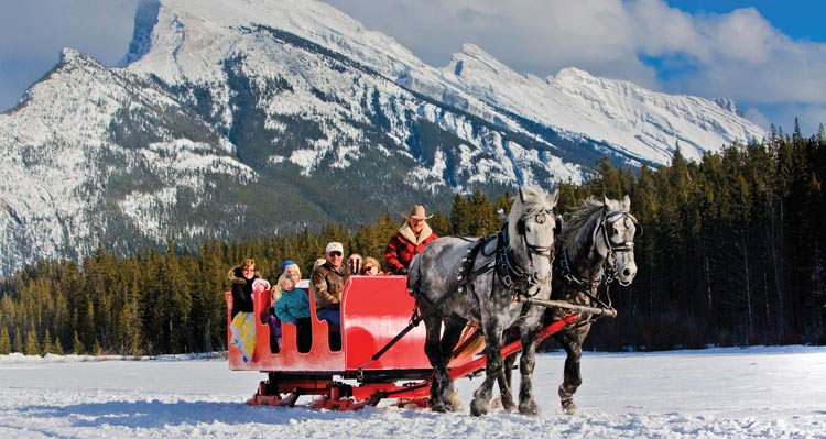 A sleigh ride below snow-covered mountains.
