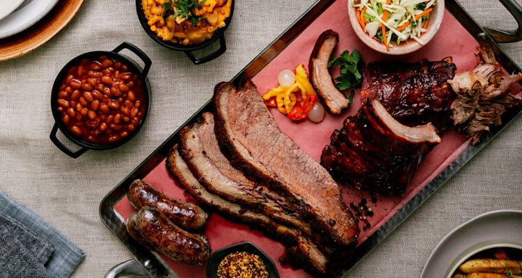 A platter of smokehouse brisket, sausages, ribs and barbecue side dishes served at the Maligne Canyon Wilderness Kitchen.