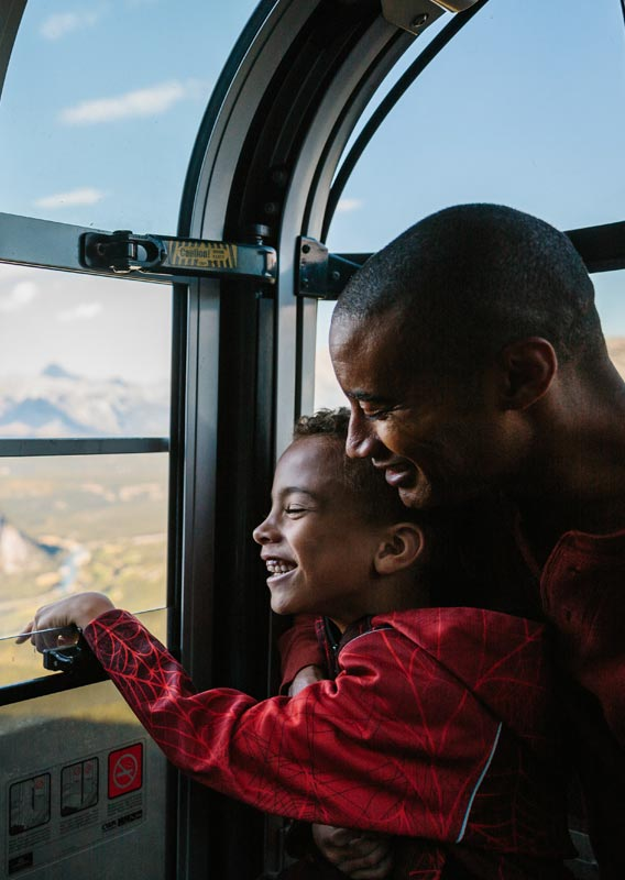 A dad and child look out the window of a Banff Gondola cabin.