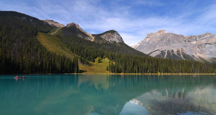 A blue lake below forested mountains.