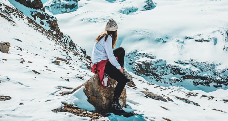 A person sits on a rock atop a snowy mountain landscape.