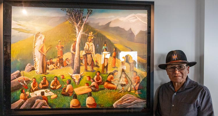 Roland Rollinmud stands in front of his painting of people gathered around a whitebark pine tree