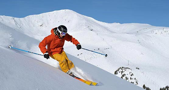 A skiier in red and yellow speeds down a snowy mountainside
