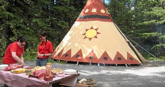 Two museum workers stand at a table outside of a tipi.