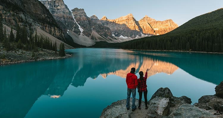 Two hikers stand on some rocks before a blue lake and jagged mountain peaks.