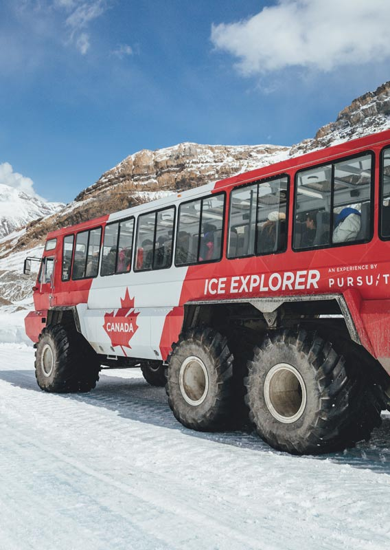 An Ice Explorer vehicle drives along an ice road on the Athabasca Glacier