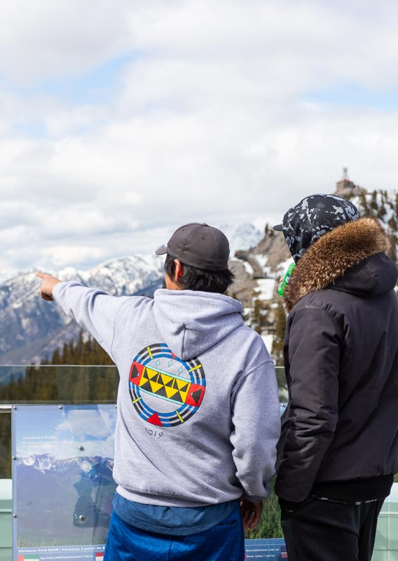 Two teenagers look out from the Banff Gondola viewing deck across a wide valley
