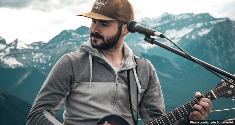 A close-up shot of Phill Nugent playing guitar in front of a mountain vista.