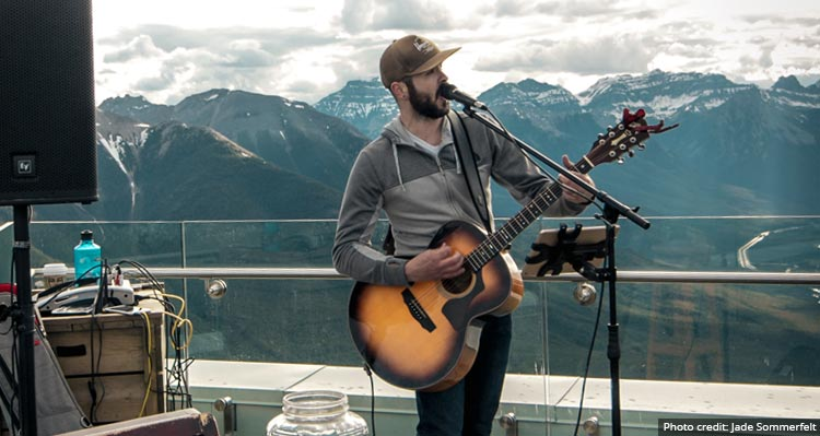 Phill Nugent plays guitar on a mountaintop terrace.