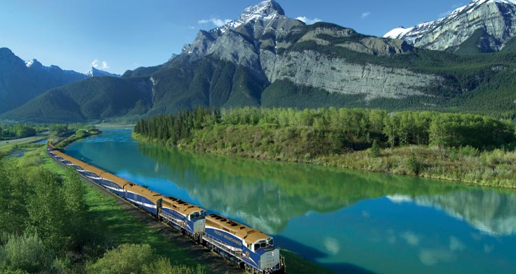 A train moves alongside a clear blue river below tree-covered mountains.