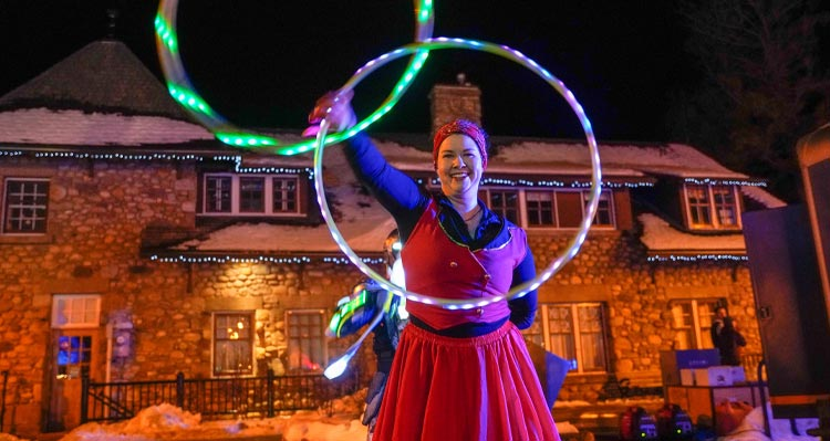 A dancer with two hoops dances on a nighttime outdoor day.
