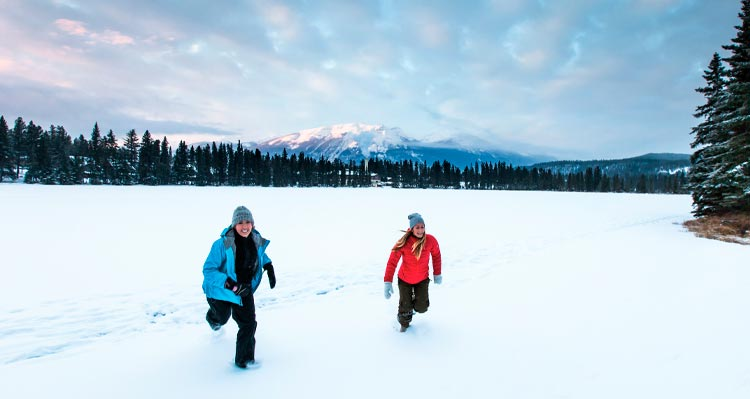Two people run across a snowy field.