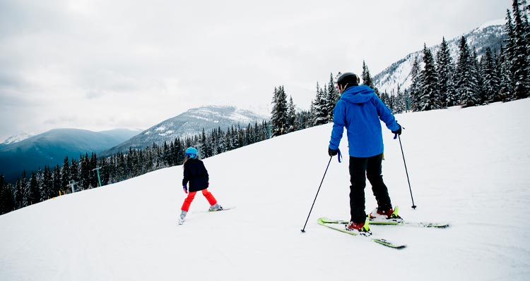 A parent and child ski down the snowy hill at Marmot Basin.