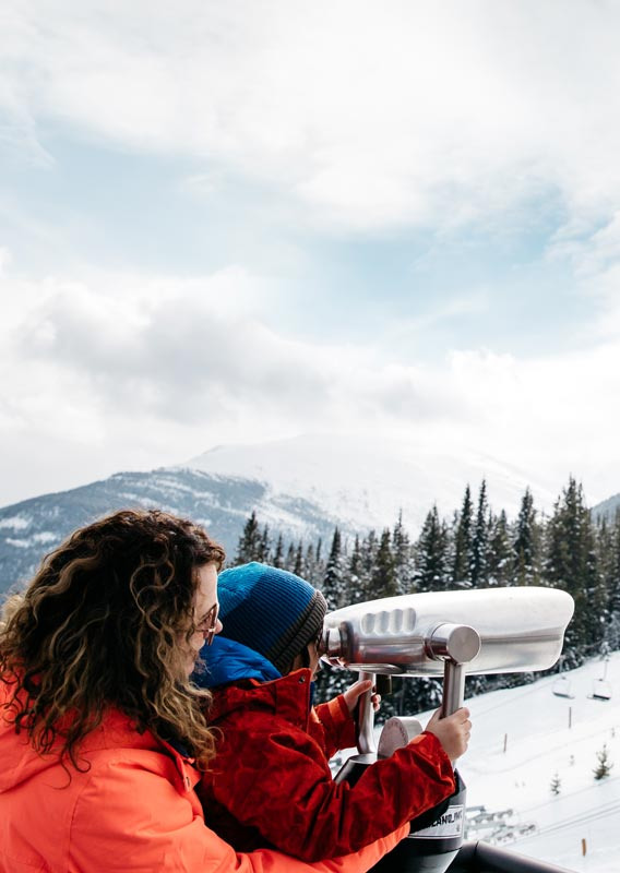 A mom and child look through sightseeing binoculars at a ski resort.