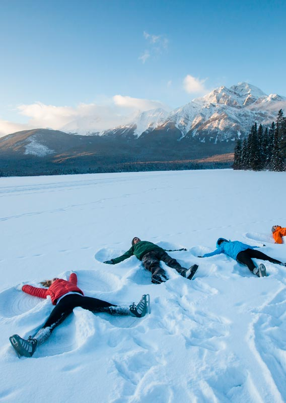 A group of people lay in the snow in front of a snow-covered mountain.
