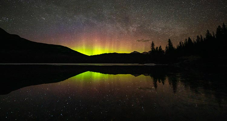 A night time view of a lake, with northern lights in the distance behind a mountain range.