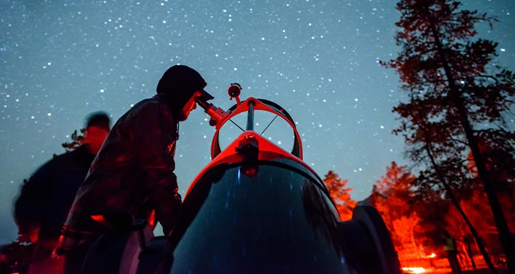 A person looks into a telescope under a starry night sky.