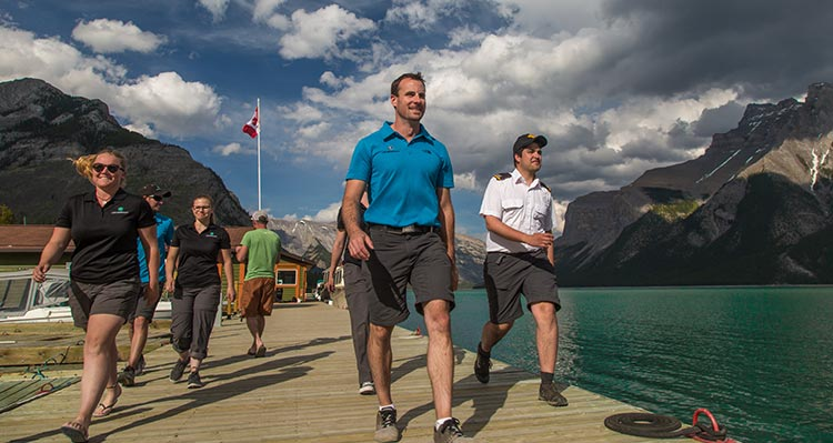 A group of people walk down a dock beside a large lake.
