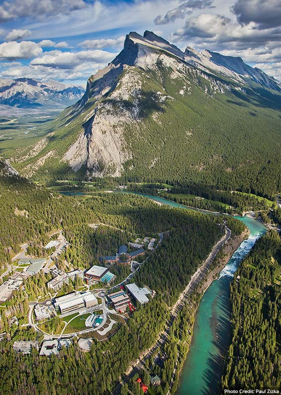 An aerial view of Banff, with Mt. Rundle rising behind a river winding through the forest.