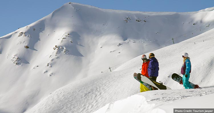 Three people with snowboards look down a run at a ski resort