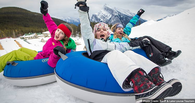 Three kids in snow tubes going down a snowy hill