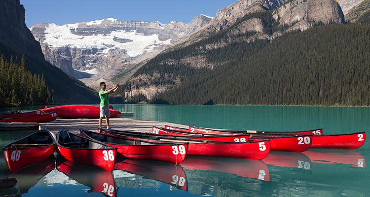 A person takes a photo from a dock with red canoes.