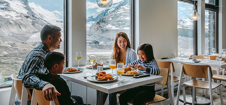 A family sits in a restaurant window with mountains in the view