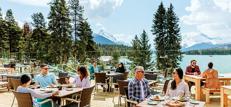 People sitting on a dining patio with mountains and a lake in the background