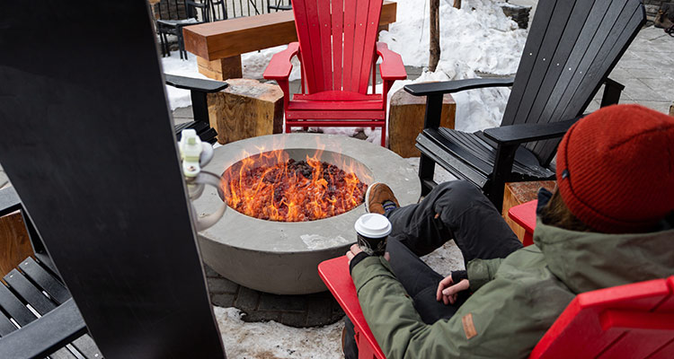 A guest sits by a fire pit with a hot beverage in hand
