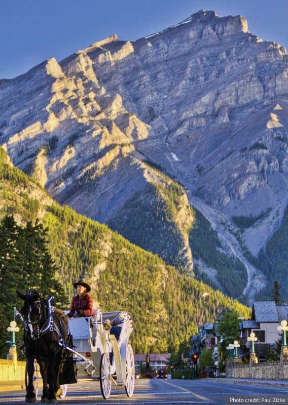 A horse and buggy stroll down a Banff street with a mountain in the background
