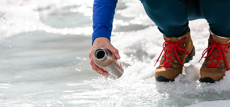 A person holds a water bottle next to ice