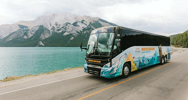 A bus drives along a road next to a large lake below a tall mountain.
