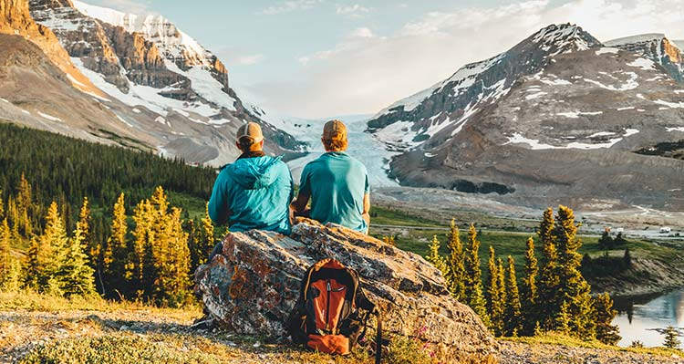 Two people sit on a rock, looking towards a glacier between tall mountains.