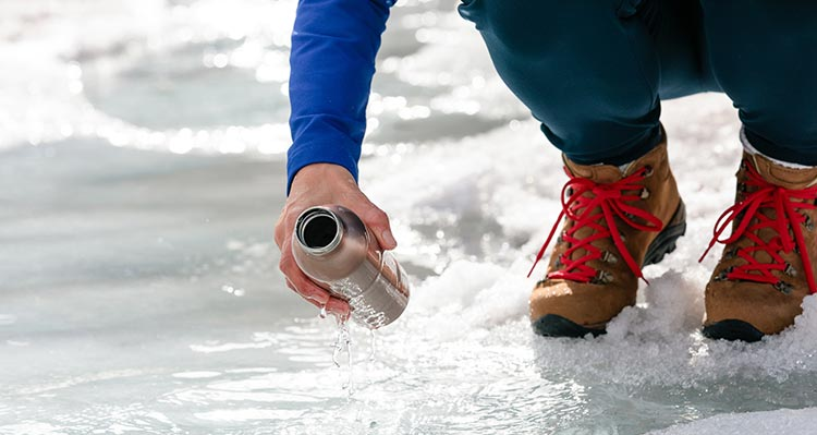 A person brings a water bottle down to water flowing from ice.