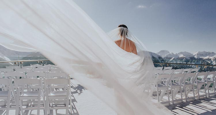 A bride walks down an aisle between chairs on a balcony overlooking mountains.