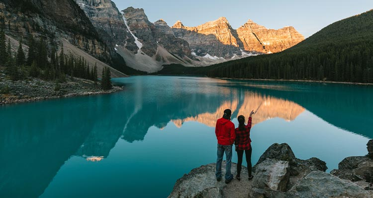 Two people stand on a lookout point above a turquoise lake below tall mountains.