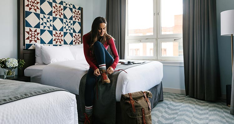 A woman sits on a hotel bed, putting on hiking boots.