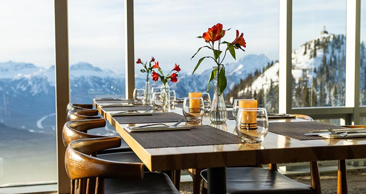 Dining tables set up with flowers along a tall window overlooking mountains and valleys.