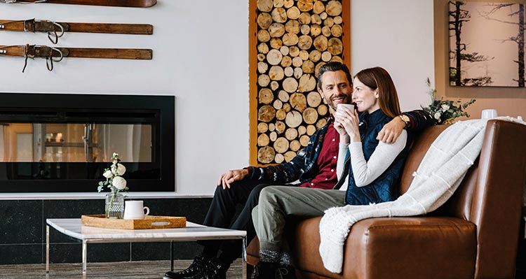 Two people sit in a lounge near a fireplace.