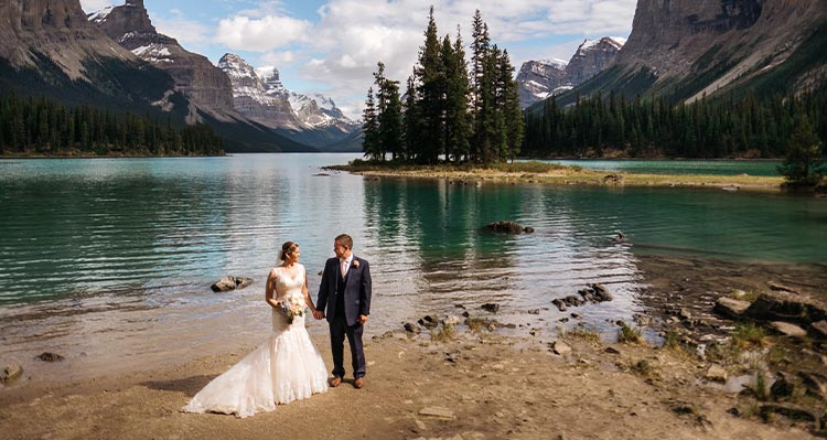A bride and groom stand on the shore of a blue lake below tall mountains.