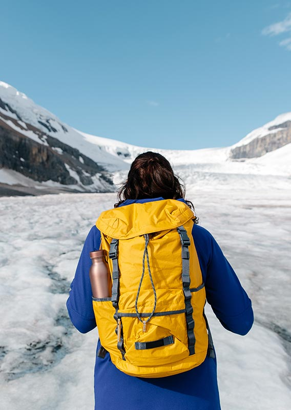 A person wearing a yellow backpack stands looking towards a glacier between mountains.